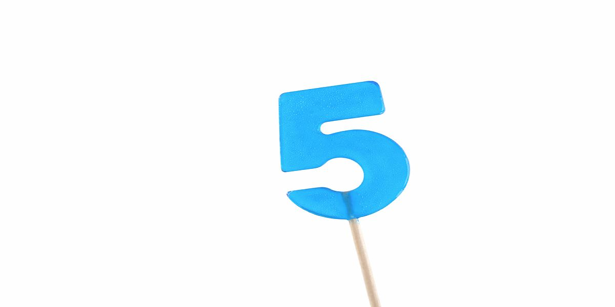 Photo of a blue, number 5 lollipop on a white stick, white background.