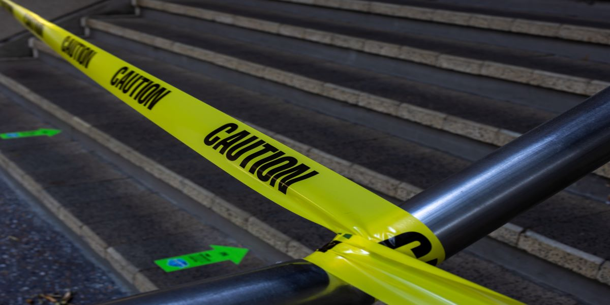 Photo of yellow and black caution tape attached to stairway handrails.