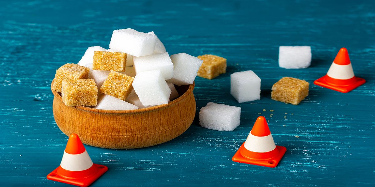 White and brown sugar cubes in a wooden bowl, sitting on a blue surface, 3 orange and white warning cones blocking the right side.