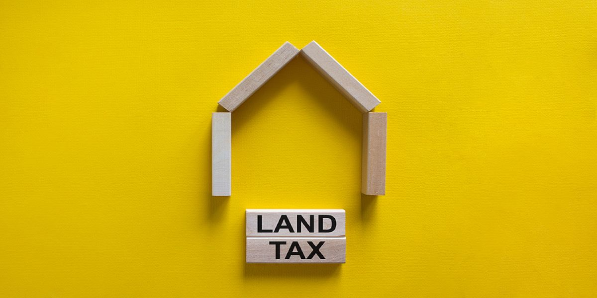 4 wooden blocks arranged in the shape of a house with a slanted roof, 1 block underneath with the words land tax printed on it, on a yellow background.