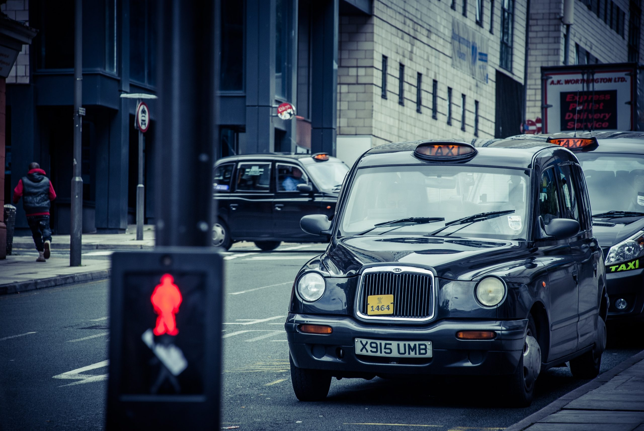 Black taxi parked by the side of the street near a pedestrian crossing.