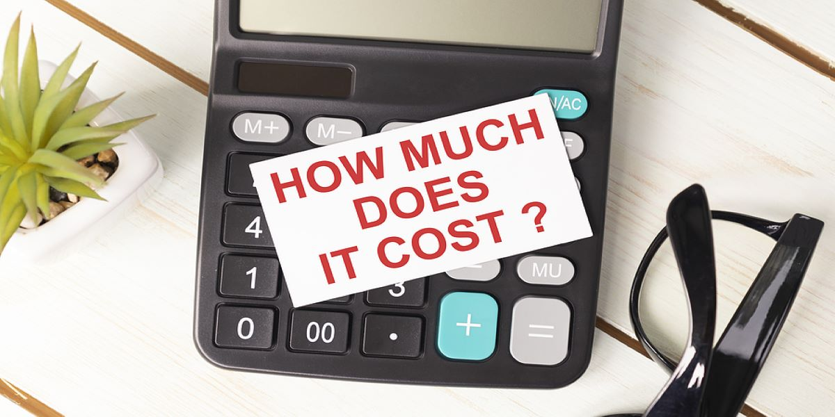 'How much does it cost?' written on a post it and stuck on a calculator.