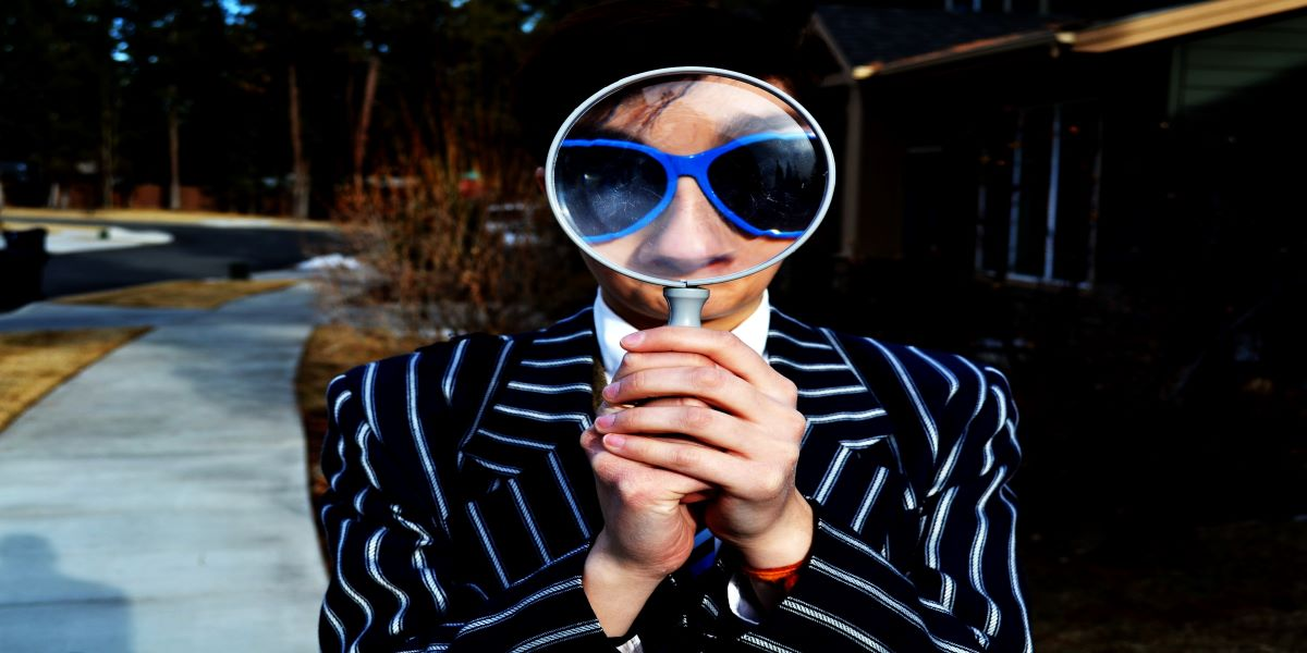 Woman wearing blue plastic sunglasses and a black, white striped suit jacket looks through a magnifying glass. Searching for lost tax.