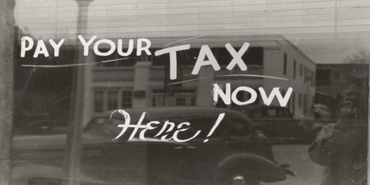 Black and white photo of an office sign painted on the window, saying Pay your tax now here!