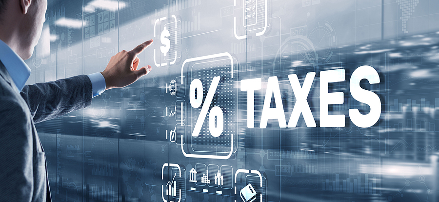 Image of man in suit pointing to a screen with the dominant text saying % taxes.
